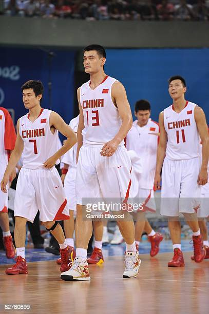 Wang Shipeng Yao Ming and Yi Jianlian of China walk on the court during the game against Spain during day 4 of the men's preliminary basketball game...
