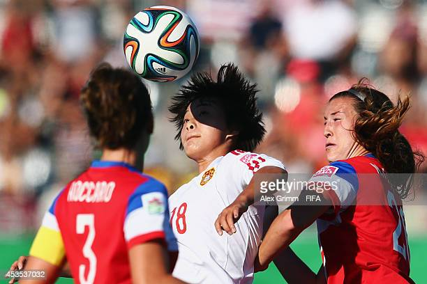 Wang Shuang of China PR is challenged by Cari Roccaro and Katie Naughton of the United States during the FIFA U20 Women's World Cup Canada 2014 group...