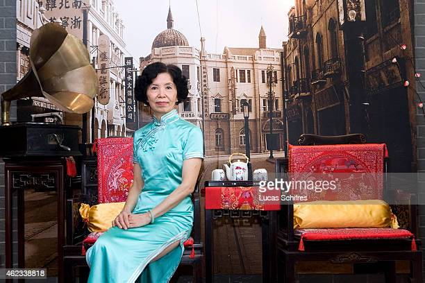 Wang Weiyu poses in a Qipao traditional dress in front of things that evoke Shanghai in the thirties ancient furniture an old record player and an...