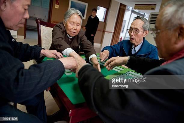 Wang Xi Heng left Liu Yu Ling Huang Ben Min 80 and Tian Bao Fa right play a game of mahjong at the Beijing Sunshine International Care House in...