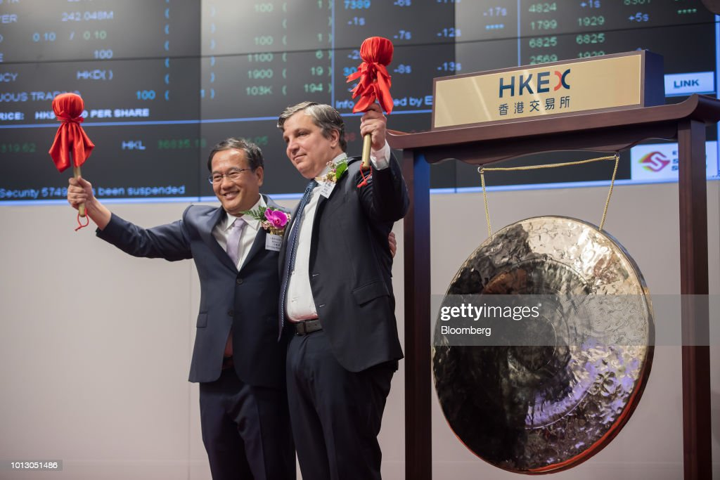Wang Xiaodong, founder and chairman of the scientific advisory board at Beigene Ltd., left, and John Oyler, founder and chief executive officer of BeiGene, pose for photographs in front of a gong during the company's listing ceremony at the Hong Kong Stock Exchange in Hong Kong, China, on Wednesday, Aug. 8, 2018. Chinese cancer drug developer BeiGene fell on its debut in Hong Kong even as its chief executive officer laid out ambitions to become a homegrown champion as well as a global company. Photographer: Paul Yeung/Bloomberg via Getty Images