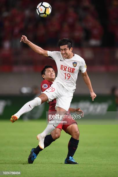 Wang Xiaolong of Tianjin Quanjian heads the ball in front of Yasushi Endo of Kashima Antlers during the AFC Champions League Round of 16 first leg...