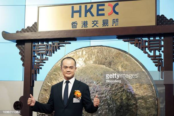 Wang Xing chairman chief executive officer and cofounder of Meituan Dianping gives the thumbs up as he poses for photographs during the company's...