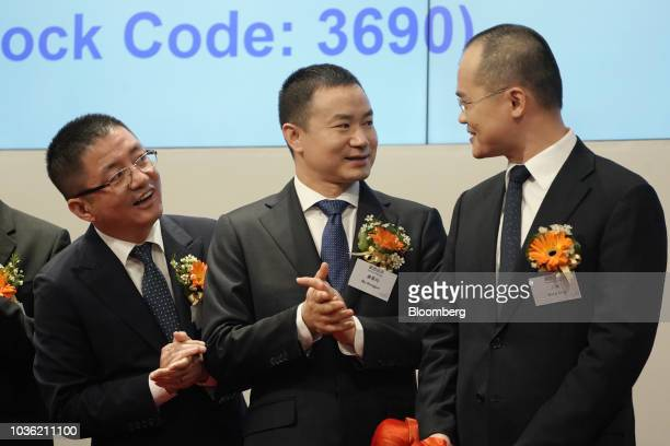 Wang Xing chairman chief executive officer and cofounder of Meituan Dianping right looks towards Mu Rongjun senior vice president and cofounder...