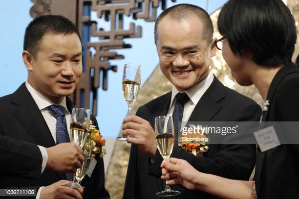 Wang Xing chairman chief executive officer and cofounder of Meituan Dianping center and Mu Rongjun senior vice president and cofounder left raise...