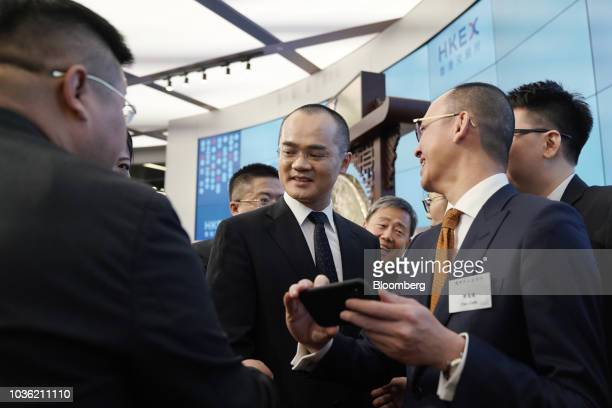 Wang Xing chairman chief executive officer and cofounder of Meituan Dianping center greets guests following the company's listing ceremony at the...