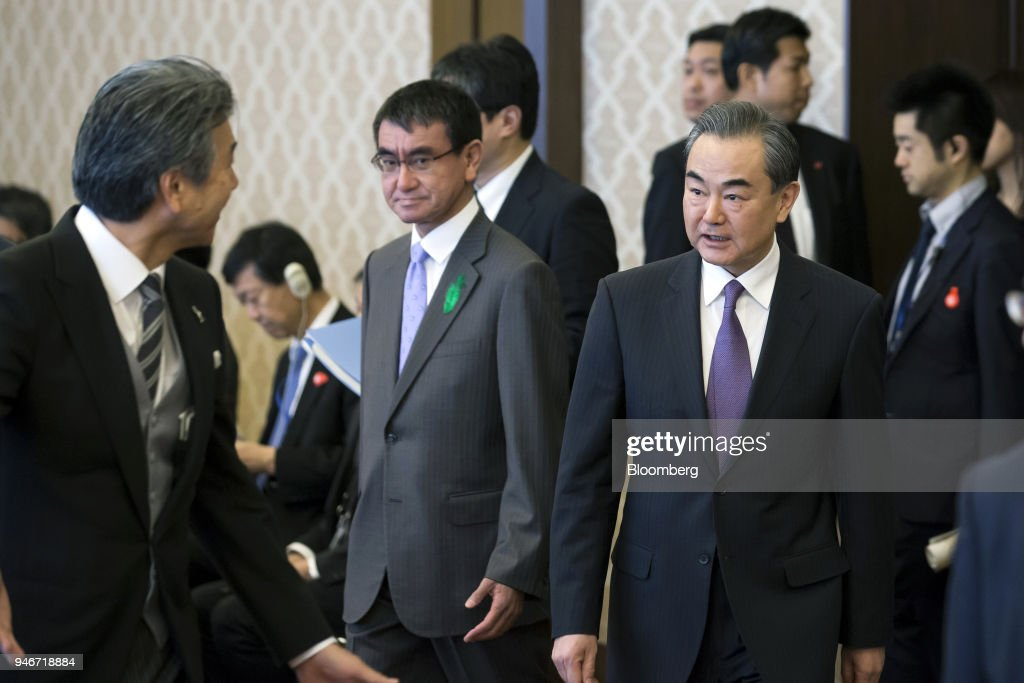 Wang Yi, China's foreign minister, center right, and Taro Kono, Japan's foreign minister, center left, arrive for a high-level Japan-China economic dialogue in Tokyo, Japan, on Monday, April 16, 2018. The foreign ministers of China and Japan agreed to work closely to push North Korea to abandon its nuclear program, in the latest sign of improved cooperation between Asia's two largest economies. Photographer: Tomohiro Ohsumi/Bloomberg via Getty Images