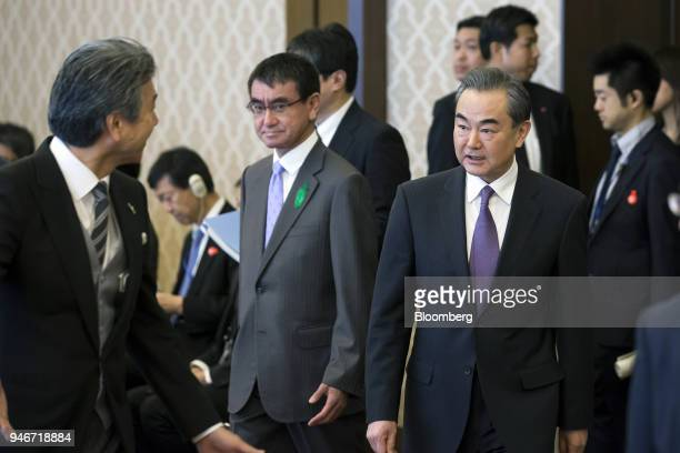 Wang Yi China's foreign minister center right and Taro Kono Japan's foreign minister center left arrive for a highlevel JapanChina economic dialogue...