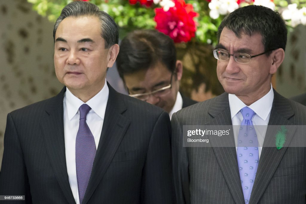 Wang Yi, China's foreign minister, left, and Taro Kono, Japan's foreign minister, right, pose for a photograph ahead of a high-level Japan-China economic dialogue in Tokyo, Japan, on Monday, April 16, 2018. The foreign ministers of China and Japan agreed to work closely to push North Korea to abandon its nuclear program, in the latest sign of improved cooperation between Asia's two largest economies. Photographer: Tomohiro Ohsumi/Bloomberg via Getty Images