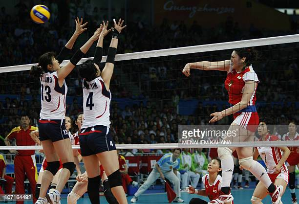 Wang Yimei of China spikes the ball against Jung Dae Young and Kim Sa Nee of South Korea during the women�s volleyball final match in the 16th Asian...