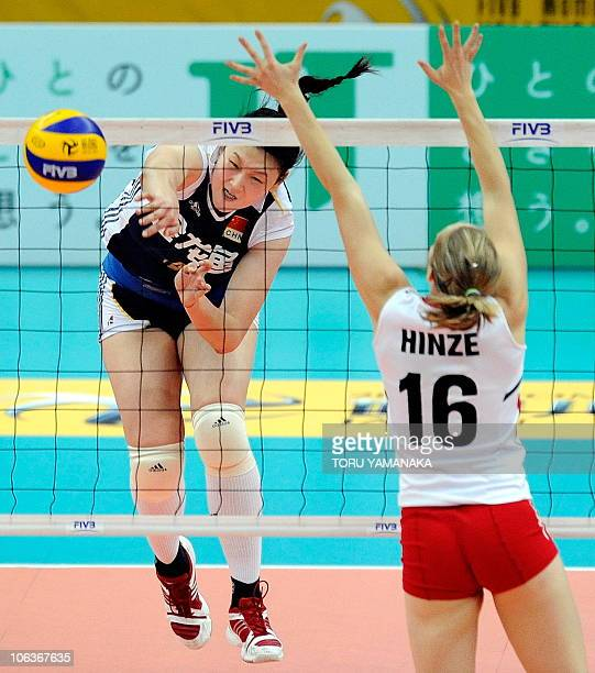 Wang Yimei of China spikes the ball over Jennifer Hinze of Canada during the first round match of the World Women's Volleyball Championship in Osaka...