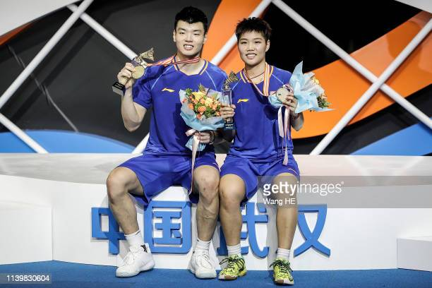 Wang Yulyu and Huang Dongping of China pose with gold medals on the podium after winning the mixed doubles final match against He Jiting and Duyue at...