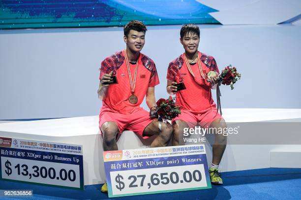 Wang Yulyu and Huang Dongping of China pose with gold medals on the podium after winning the mixed doubles final match against Tontowi Ahmad and...