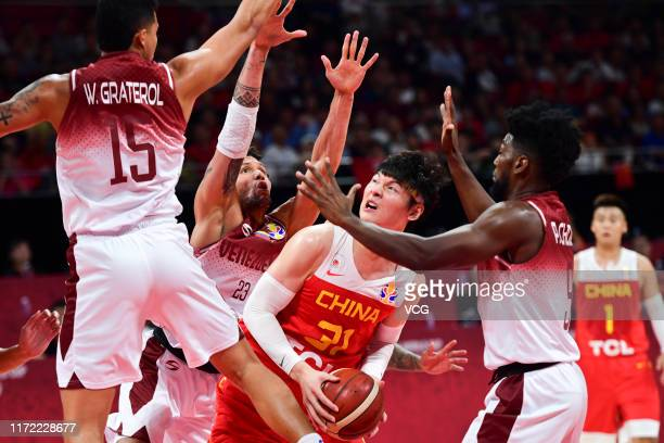 Wang Zhelin of China drives the ball against Michael Carrera and Windi Graterol of Venezuela during FIBA World Cup 2019 Group A match between...