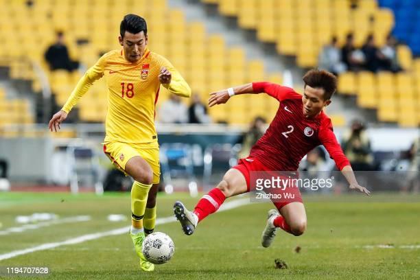 Wang Ziming of China competes for the ball with Tsui Wang Kit of Hong Kong during the EAFF E-1 Football Championship match between Hong Kong and...