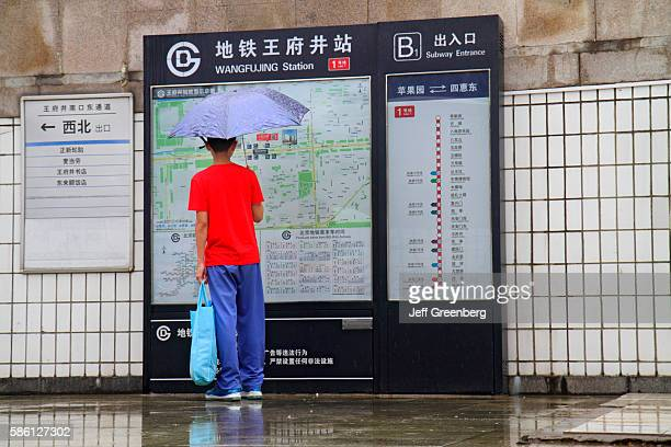 Wangfujing Subway Station Line 1 Asian teen boy with umbrella