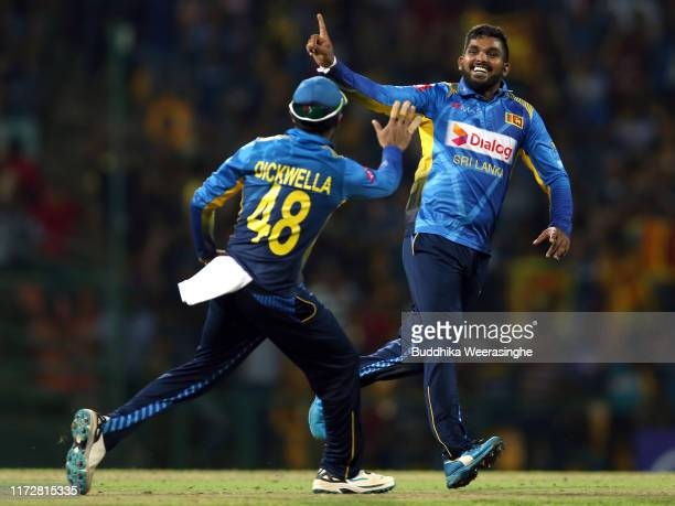 Wanidu Hasaranga of Sri Lanka celebrates with his team mate Niroshan Dickwella after taking the wicket of New Zealand's Todd Astle during the...