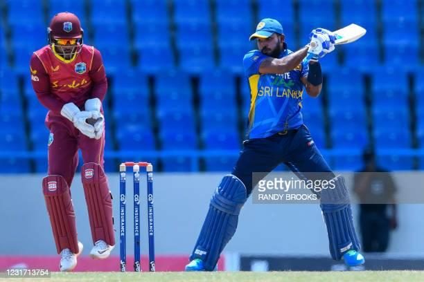 Wanindu Hasaranga of Sri Lanka hits 4 as Shai Hope of West Indies watch during the 3rd and final ODI match between West Indies and Sri Lanka at...