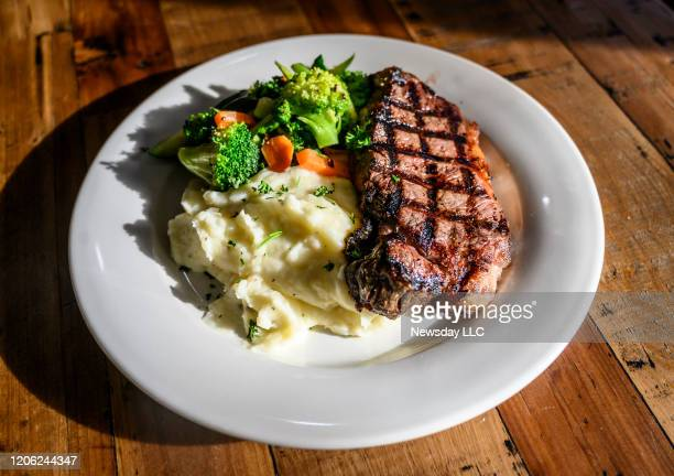 Photo of a plate of grilled shell steak with mashed potatoes and sauteed vegetables at Holy Smoke Grill in Wantagh, New York on January 23, 2020.