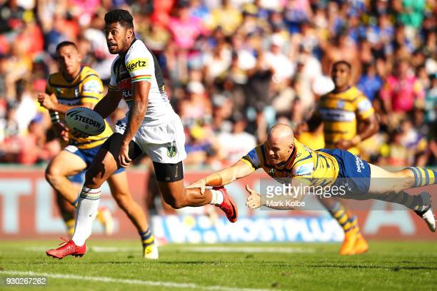 Waqa Blake of the Panthers evades the tackle of Beau Scott of the Eels on his way to scoring a try during the round one NRL match between the Penrith...