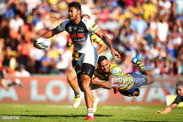 Waqa Blake of the Panthers evades the tackle of Bevan French of the Eels on his way to scoring a try during the round one NRL match between the...