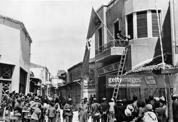 War 1939-1945. Invasion of the Greece by Germans. German troups runing up flags with swastika on the Market place of Moudros in the Lemnos island....
