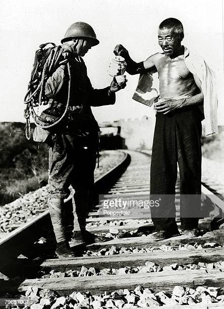 War and Conflict 2nd SinoJapanese War A Japanese railroad guard is refreshed by a cup of tea from a friendly chinese near Tientsin Northern China...