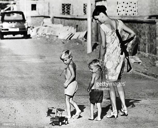 War and Conflict Aden A mother carrying a machine gun over her shoulder walks with her two children along a road in Aden