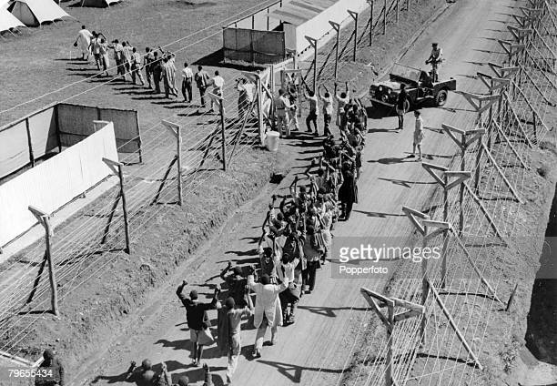 24th April 1954 Suspects are marched into Langata Detention Camp Nairobi where suspected Mau Mau terrorists are held The emergeny in Kenya was due to...