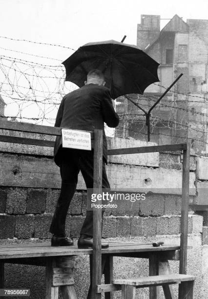 War and Conflict People The Berlin Wall pic 6th October 1962 A man on raised platform peers over the wall holding an umbrella as the East German...