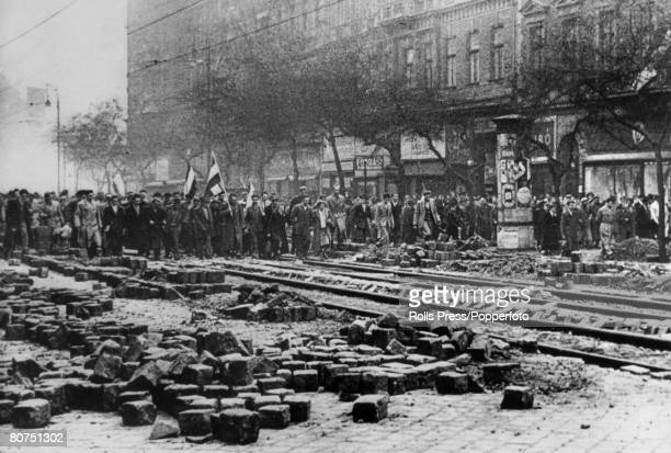 October 1956 The Hungarian Uprising A large crowd of angry Hungarian rebels marching through a rubble stren Budapest street