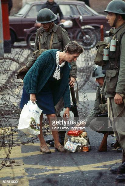 1969 Belfast Northern Ireland With the threat of bombs constant a local woman is stopped and her shopping checked by British soldiers as she passes...