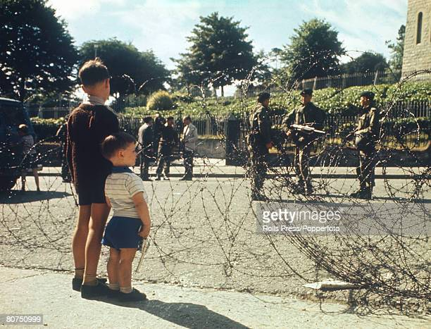 War and Conflict, Social History, pic: 1969, Belfast, Northern Ireland, Two little boys seem bewildered as they stare across the barbed wire at...