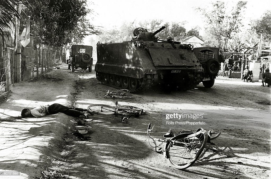 War and Conflict The Vietnam War. Da Nang, South Vietnam. pic: January 1968. A young man lies dead by the side of the road as a South Vietnamese tank and infantry search for the Viet Cong enemy. : News Photo