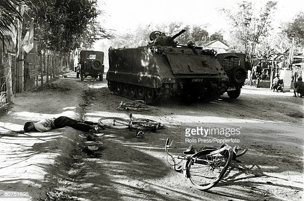 War and Conflict The Vietnam War Da Nang South Vietnam pic January 1968 A young man lies dead by the side of the road as a South Vietnamese tank and...