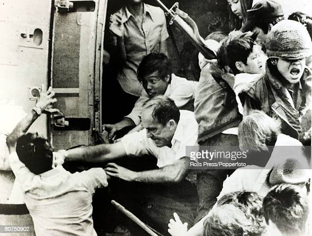 War and Conflict, The Vietnam War, pic: 1975, Nha Trang, South Vietnam, An American official punches a man in the face as an already overloaded...