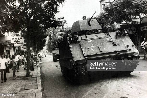 1975 Saigon South Vietnam Communist Provisional Revolutionary Government soldiers drive a captured armoured personnel carrier through the streets of...