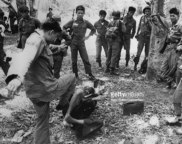 April 1965 An Ninh South Vietnam An 'interrogation' in progress as a South Vietnamese interrogator kicks a Viet Cong suspect as others idly watch
