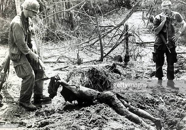 April 1968 My Xa South Vietnam An American soldier of the 101st Airbone drags the body of a dead Viet Cong from a grave the freshly dug grave had...
