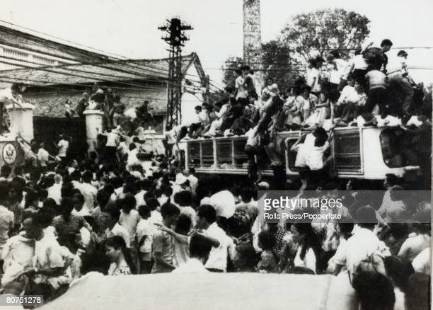 April 1975 Saigon South Vietnam Vietnamese civilians climb aboard a bus and clamber on the roof in an attempt to enter the relative safety of the...