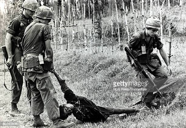 circa 1968 South Vietnam American troops pull the body of a dead Viet Cong from his hideout