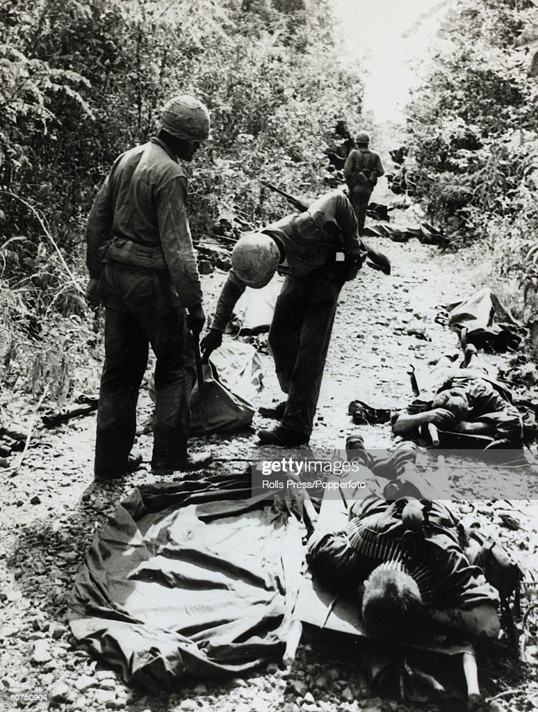War and Conflict The Vietnam War. pic: December 1965. Michelin Plantation, South Vietnam. Dead and wounded Americans on a jungle track after a Viet Cong ambush, as US. 1st Army Infantry comrades check bodybags : News Photo