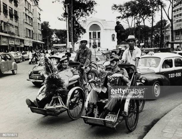 December 1966 Saigon South Vietnam Two Australian soldiers riding in pedicabs having been christmas shopping in the city