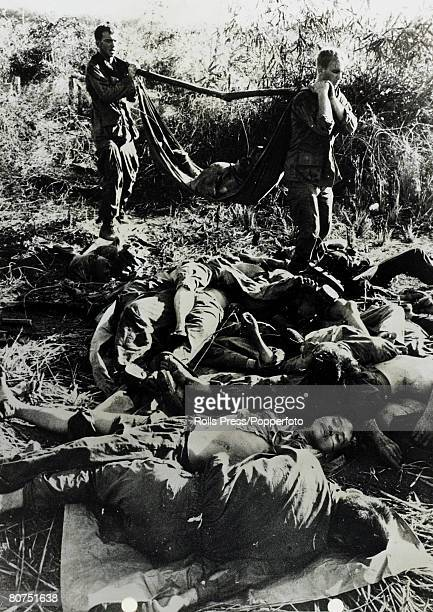 December 1967 Bu Dop South Vietnam American soldiers if the 1st US Infantry Division carry away a wounded Viet Cong as a pile of dead Viet Cong are...
