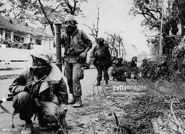 December 1967 Hue South Vietnam US marines wearing gas masks as they are about to use teargas to flush a sniper out of a house