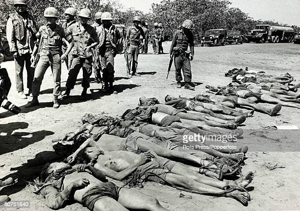 December 1967 Phuc Tho South Vietnam Thai members of the Queen's Cobras view the bodies of dead Viet Cong who had tried to storm their camp near...