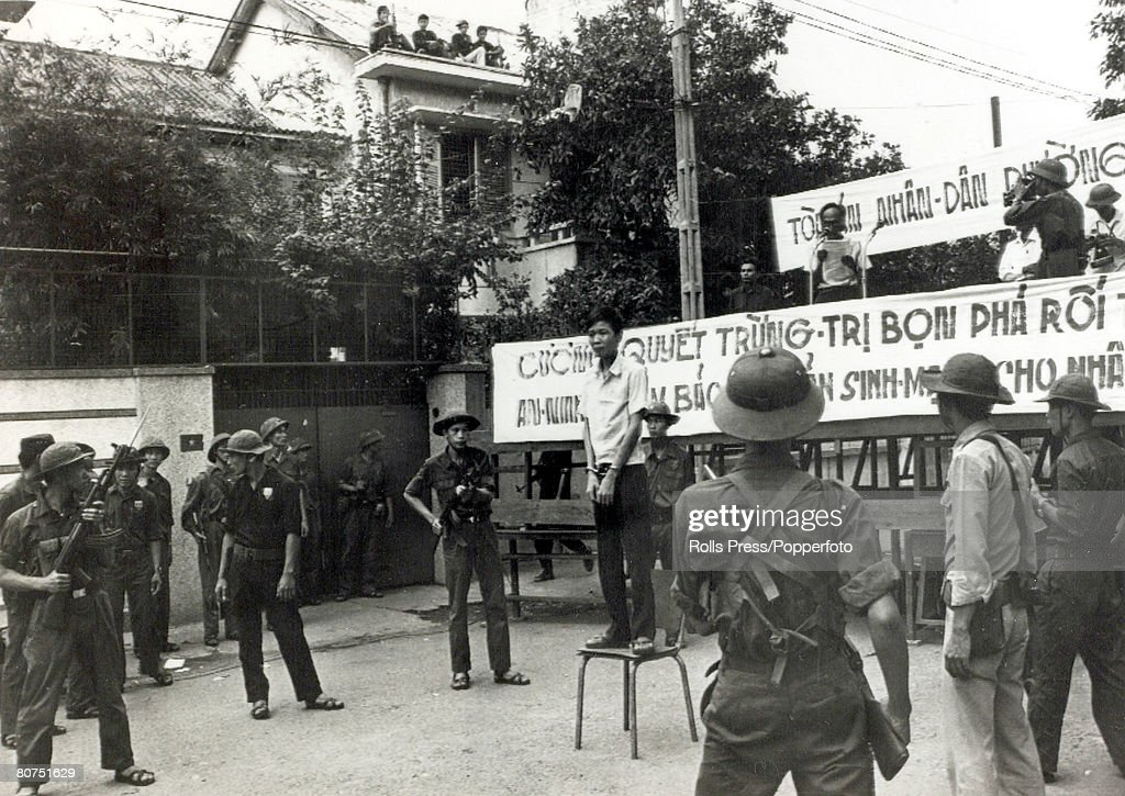 War and Conflict The Vietnam War. pic: June 1975. Nguyen Tu Sang, Saigon, Vietnam. A man stands on a chair, convicted of armed robbery as an official reads his sentence from a platform, as communist forces prepare to act as a firing squad and carry out t : Nachrichtenfoto
