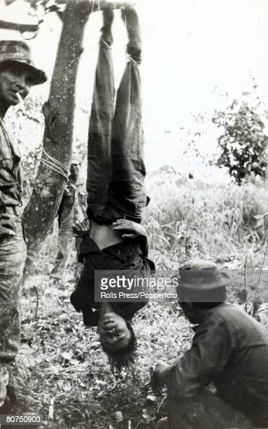 May 1966 Duc Phong South Vietnam Chinese mercenaries working with US Special Forces string up a Viet Cong suspect by the ankles during an...