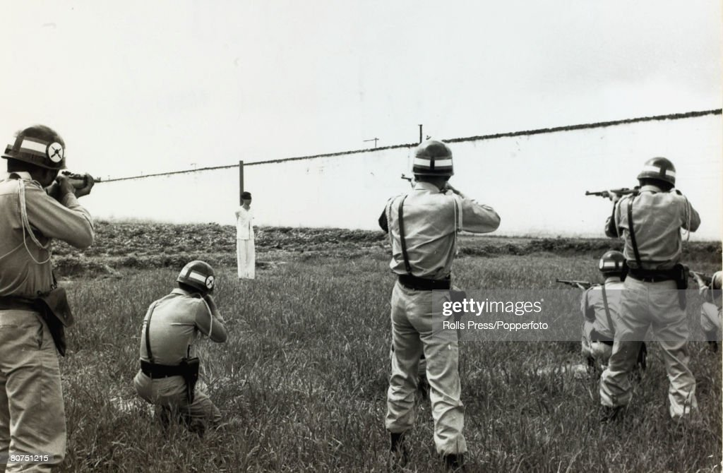 War and Conflict The Vietnam War. pic: October 1964. Saigon, South Vietnam. A blindfolded convicted terrorist faces a firing squad as the executioners take aim. : News Photo