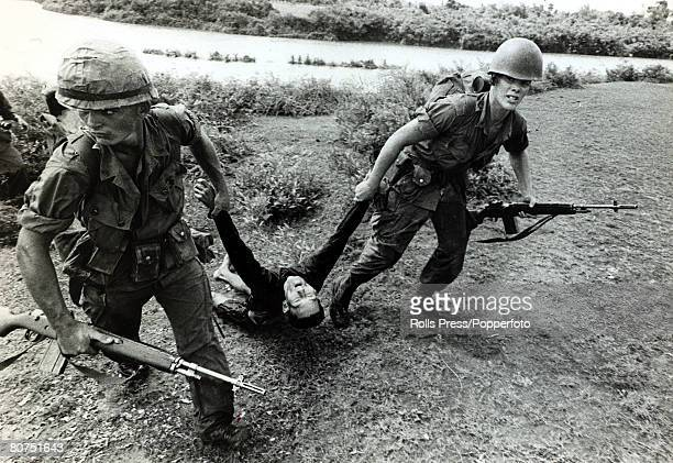 October 1965 Chu Lai South Vietnam Two US marines drag away a dead Viet Cong from a river after he had tried to escape by swimming across